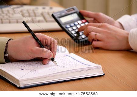 Primer plano del escritorio de oficina con las manos, calculadora, papeles y teclado