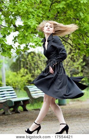 Beautiful young caucasian model with long flying hair in park