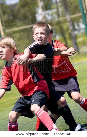 Teenage boys playing soccer at sunny day