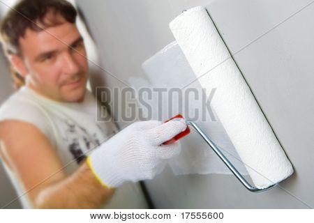 Fröhlich Arbeitnehmer Malerei eine Wand mit Walze