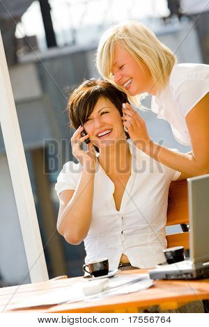 Beautiful brunette talking by phone and smiling blonde holding another cellphone near her ear