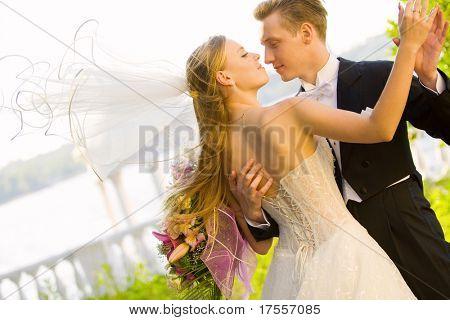 Foto de casamento colorido da noiva e do noivo beijando