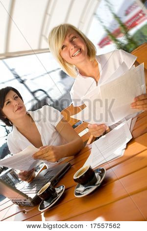 Two attractive girls with laptop and paperworks drinking coffee