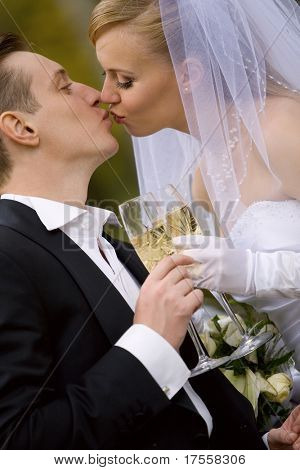 Colorful wedding shot of bride and groom kissing
