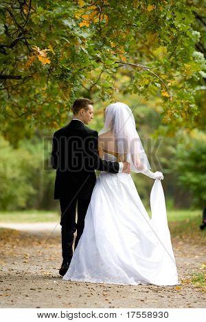 bride and groom walking across park