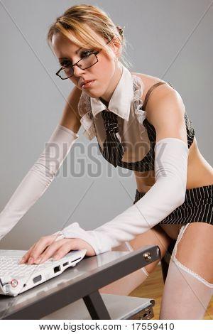 Sexy girl wearing very short skirt pretending to work on laptop
