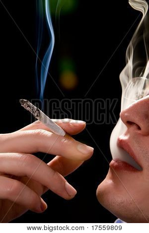 Man holding smoking cigarette over black