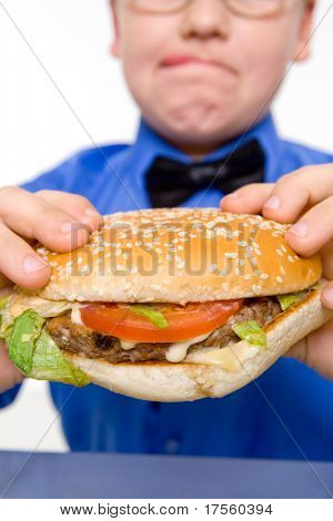 Young fat school boy eating hamburger