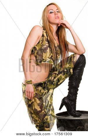 Cool blond woman wearing khaki setting boot over metal barrel