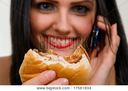 Attractive young lady eating burger, holding mobile phone