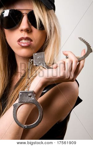 "Blonde ""police"" girl with handcuffs isolated on white"
