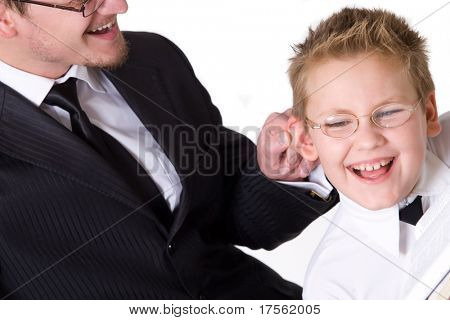 Father squeezing his son ear jokingly pretending to punish him