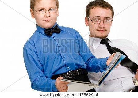Father and son reading a magazine isolated on white
