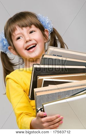 Pretty little girl holding stack of books