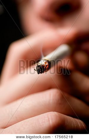 Man lighting a cigarette over black