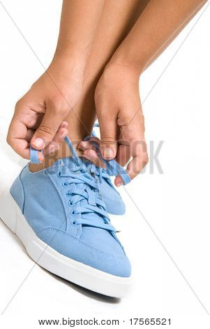 Woman tightening laces on sport shoe