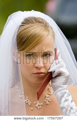 Beautiful upset bride talking on cellphone
