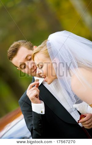 Young groom giving a chocolate candy to bride