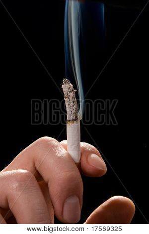 Man holding smoking cigarette over black