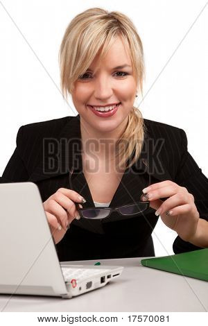 Pretty young blond holding eyeglasses looking at laptop screen