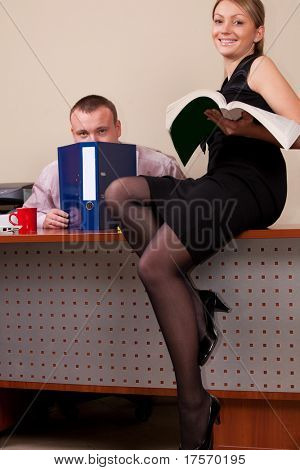 Young woman sitting on her male coworker desktop