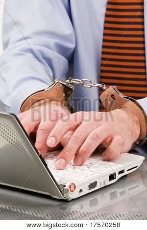Businessman's hands bound to laptop with handcuffs