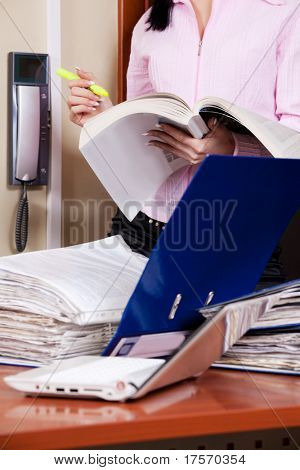 Female accountant with desk overloaded with papers in front