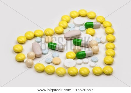 Various color tablets and capsuls in the shape of a heart on white background