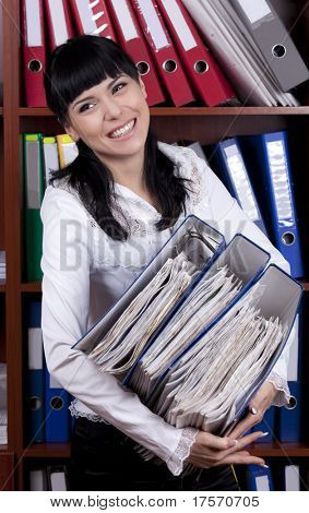 Smiling young secretary overloaded with files