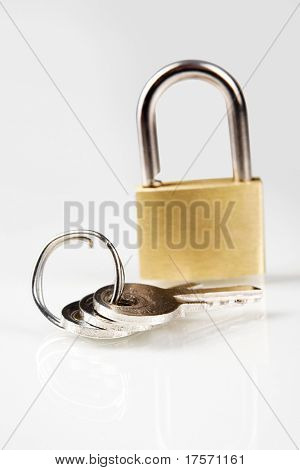 Metal padlock over white with keys