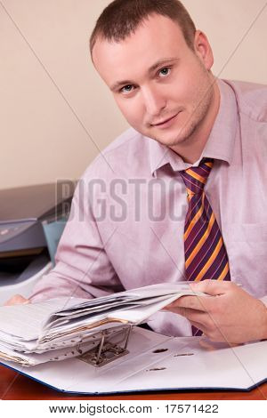 Handsome young office worker sitting at desktop