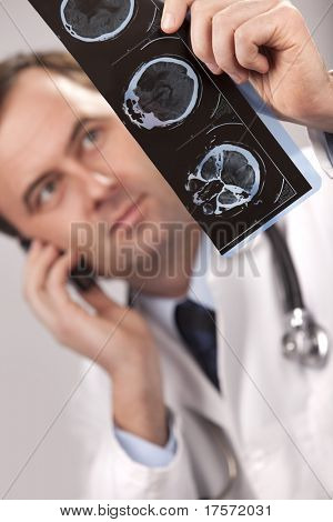 Doctor is checking  x- ray computed tomography, while talking on a cellphone. Horizontal studio shot.