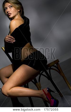 Picture of sensual young woman in black sitting on a chair and looking away