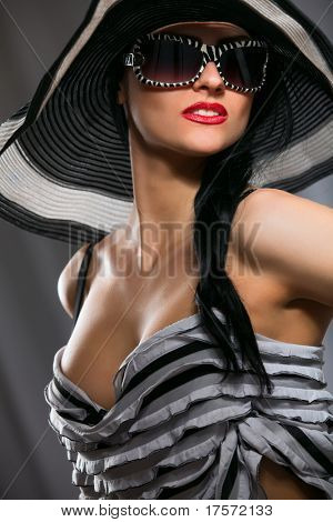 Beautiful model in striped hat and top with glasses on the gray  background