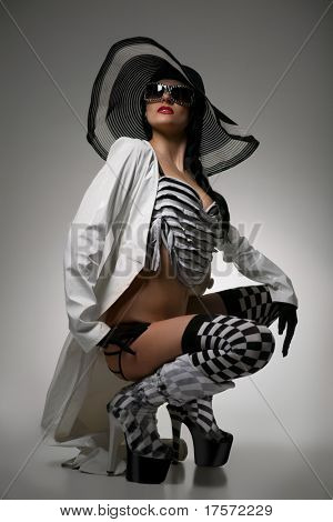 Beautiful model in striped hat, black-and-white suit and glasses on the gray  background