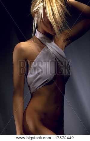 Passionate woman fluffing up blond hair, both hands risen behind head