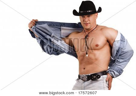 A muscular man in a cowboy hat and denim. Isolated on white.