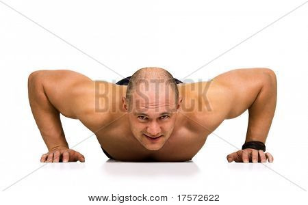 Front view of strong, handsome man doing push-ups as bodybuilding exercise, training his muscles. Isolated on white.