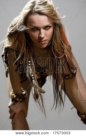 Portrait of a passionate amazonian woman fluffing up her hair, both hands risen behind head