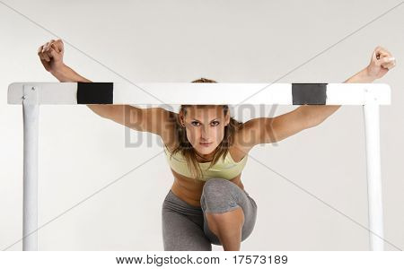 Pretty caucasian sportive model with hurdle, over gray background