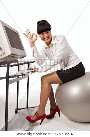 Smiling business woman doing exercise with a grey workout ball, showing okay sign, working on a computer, over white background