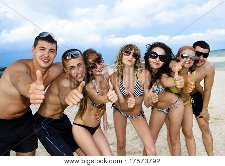 Joyful team of friends having fun at the beach and showing okay sign