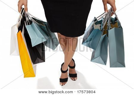 Waist-down view of young woman carrying shopping bags