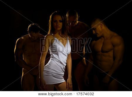Beautiful young woman against three athletes, bowing their heads respectfully before her