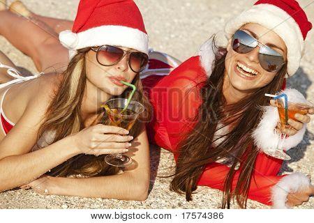 Dos jóvenes hermosas mujeres en Navidad traje con vaso de martini en primera línea de playa