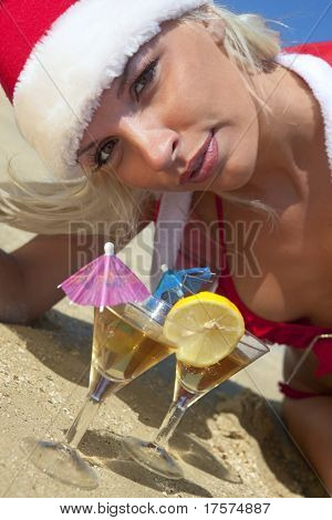 Young sexy women in christmas suit with two martini glasses on the beachfront