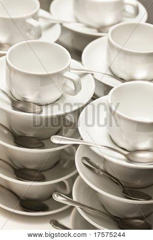 Apilados tazas vacías con cucharaditas en una función sobre fondo blanco