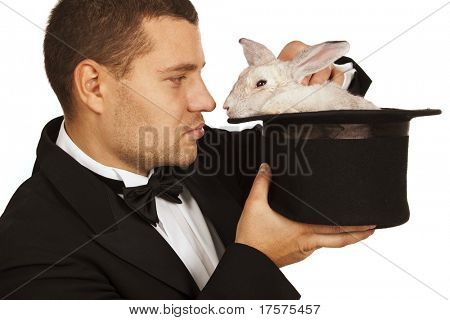 man dressed as a magician face to face with a rabbit in a top hat isolated over a white background