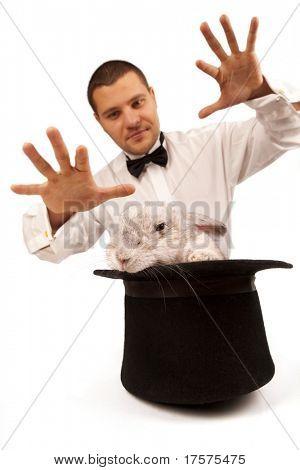 Homem vestido como um mago de magia com um coelho em uma cartola isolado sobre um fundo branco