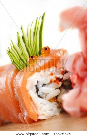 Red sushi  Dragon devouring ginger on a wooden board against white background